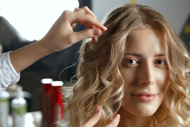 高級美容院でプロの美容師から髪型を取得している愛らしい若いブロンドの女性。クローズアップショット