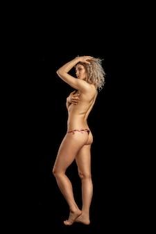 검은 배경에 스튜디오에서 완벽한 엉덩이와 귀여운 팬티에 곱슬 머리를 가진 사랑스러운 젊은 금발의 여자