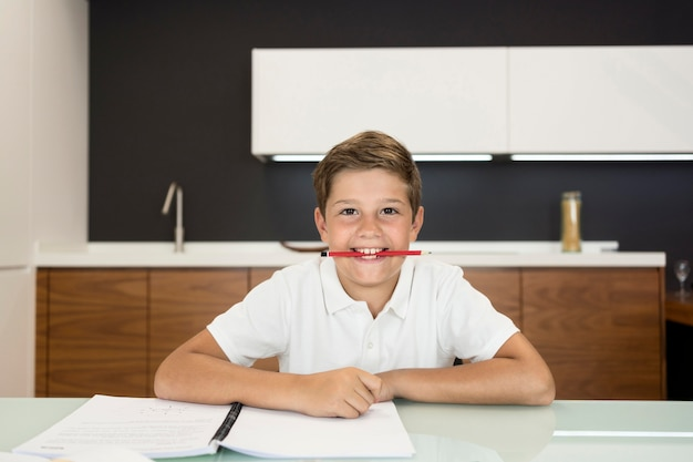 Прелестный молодой мальчик делает свою домашнюю работу