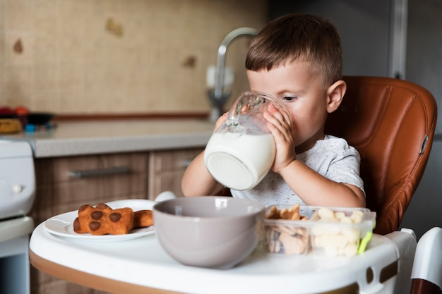 Adorable young boy drinking milk