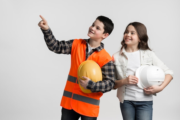 Adorable young boy and girl holding hard hats