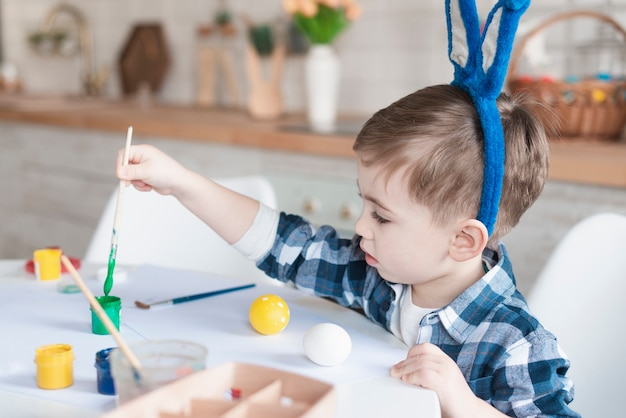 Adorable young boy painting easter eggs