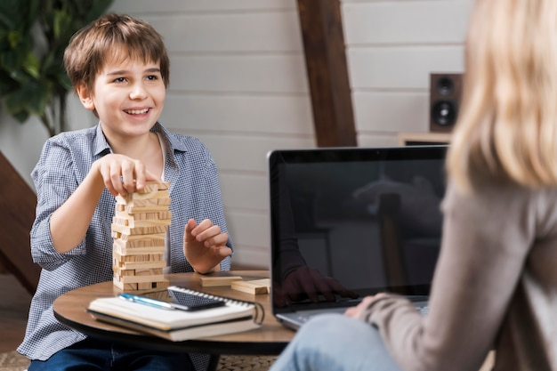 Adorable young boy playing jenga while mother is working