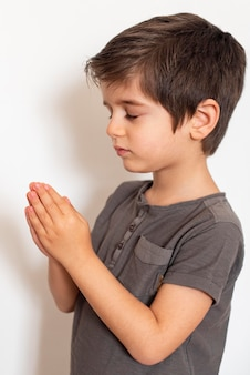 Adorable young boy praying at home
