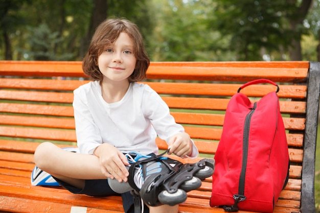 Adorable young boy smiling to the camera, putting on rollerskates at the park