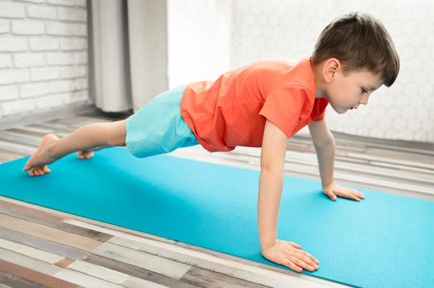 Прелестный мальчик тренируя детенышей дома