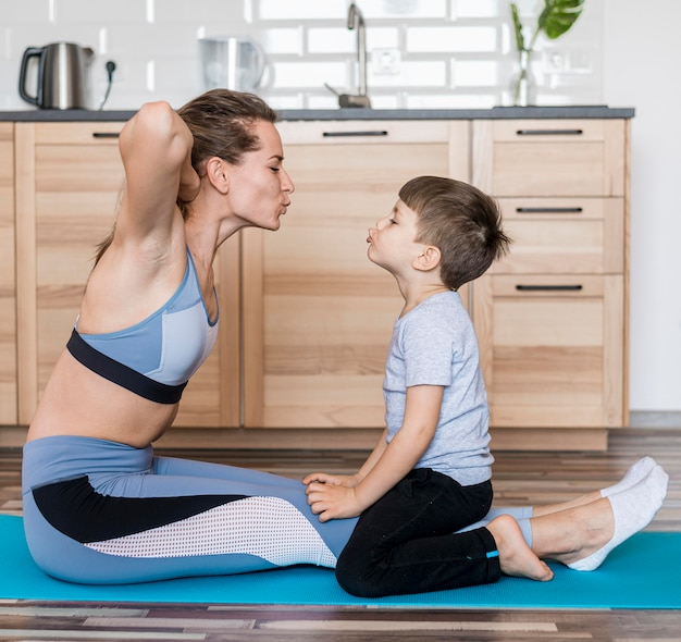 Adorable young boy training together with mom