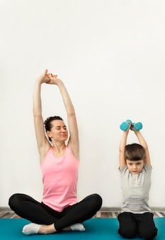 Adorable young boy training together with mother
