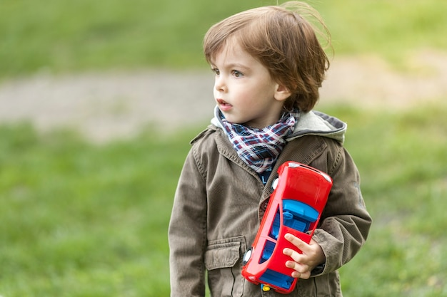 Adorable young boy with toy car looking away