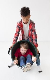 Adorable young boys playing together with recycle bin