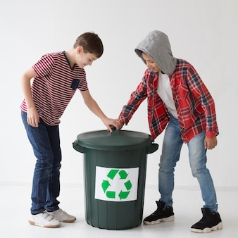 Adorable young boys touching recycle bin
