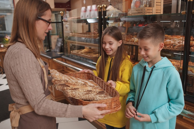 Adorable young brother and sister choosing fresh bread from the basket female baker is holding
