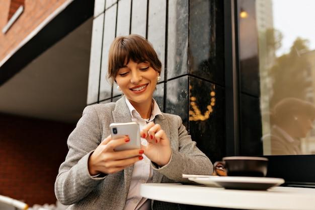 Adorabile giovane signora bruna in giacca grigia e camicia bianca utilizza lo smartphone e lavora nel computer portatile