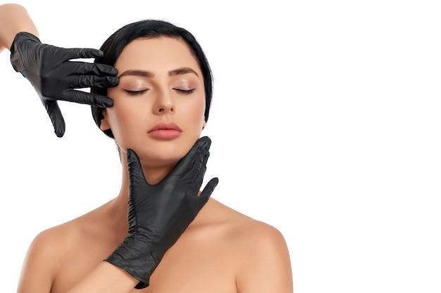 Очаровательная молодая брюнетка со здоровой чистой кожей позирует с руками косметолога в черных перчатках вокруг ее лица