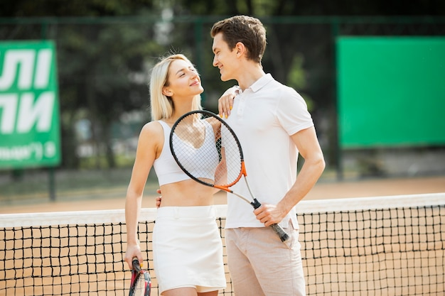 Очаровательная молодая пара на теннисном корте