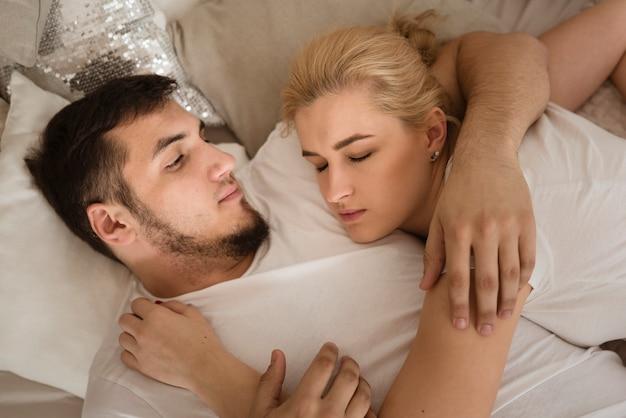 ベッドで一緒に愛らしい若いカップル
