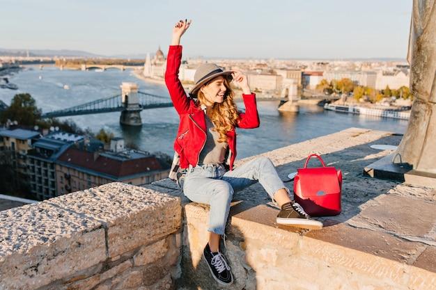 Adorabile giovane modella con capelli castano chiaro che esprime emozioni felici, viaggiando in europa