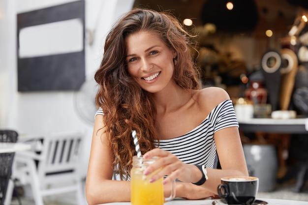 Очаровательная молодая женщина с темными длинными волосами, одетая в полосатую футболку в кафе, пьет свежий сок и эспрессо.