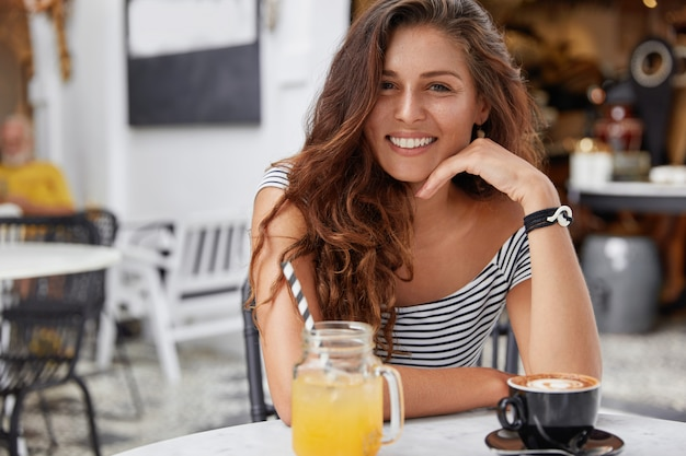 Adorable young female with dark long hair, dressed in striped t- shirt in coffee shop, drinks fresh juice and espresso.