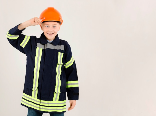 Adorable young fireman copy space