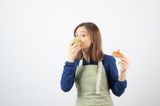 Adorabile ragazza in grembiule che mangia mela verde invece di pizza.