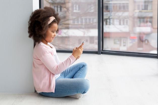 愛らしい少女の携帯電話の閲覧
