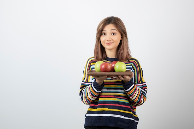 Adorable young girl in casual clothes holding colorful apples.