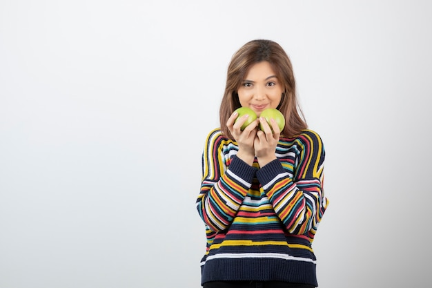 Adorable young girl in casual clothes holding green apples on white.