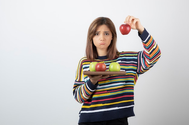 Adorable young girl in casual clothes showing red apples over white wall.