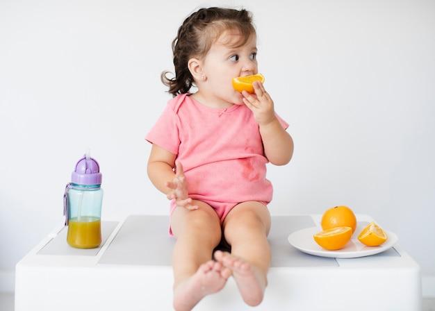 オレンジを食べる愛らしい少女