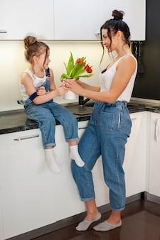 Очаровательная молодая девушка дарит цветы матери