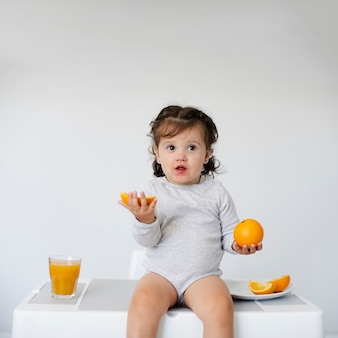 Adorable young girl holding oranges