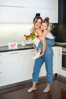 Очаровательная молодая девушка обнимает мать