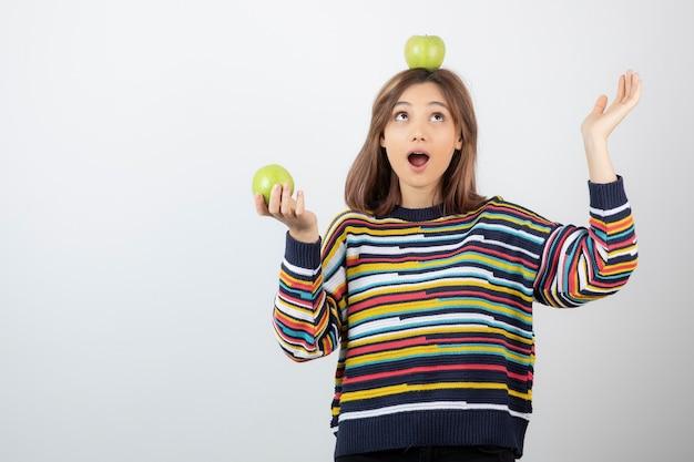 흰색에 녹색 사과를 보고 평상복을 입은 사랑스러운 어린 소녀.
