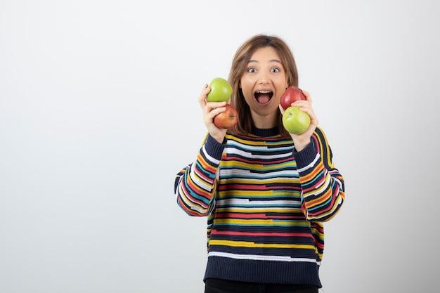 화려한 사과와 함께 포즈를 취하는 캐주얼 옷을 입은 사랑스러운 어린 소녀.