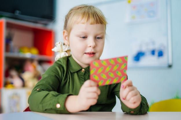 사랑스러운 어린 소녀는 밝은 카드에서 찾고 있습니다. 유치원 개념. 아이의 교육.
