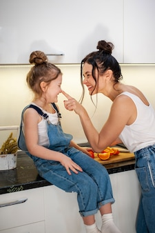Adorable young girl and mother together in kitchen
