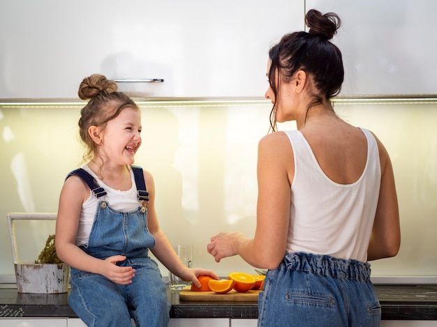 Adorable young girl playing with mother in the kitchen