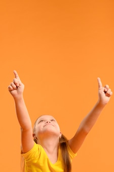 Adorable young girl pointing up with copy space