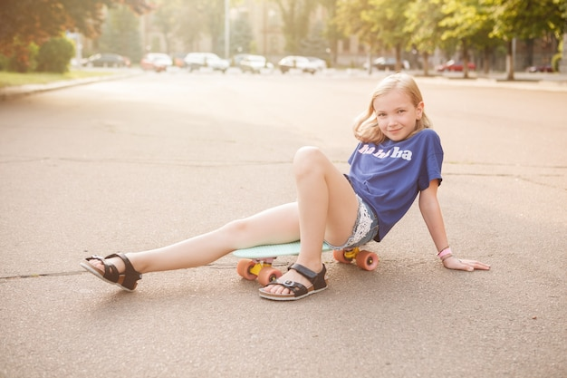 Adorable young girl smiling, sitting on her pennyboard in the city