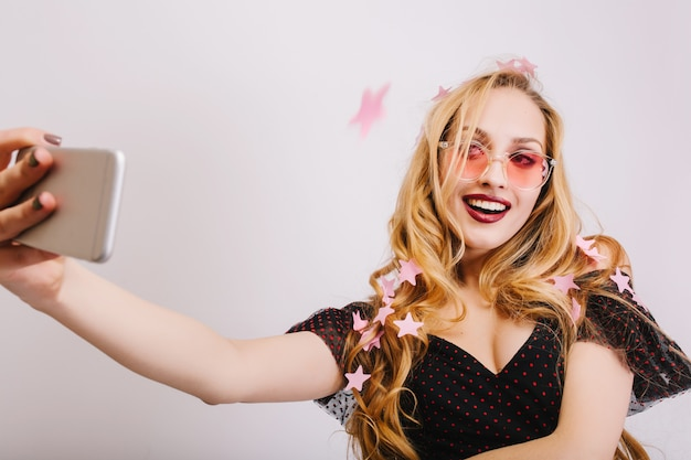 Adorable young girl with blonde long curly hair taking selfie at party, smiling, covered with pink stars confetti. wearing colorful glasses, black dress.