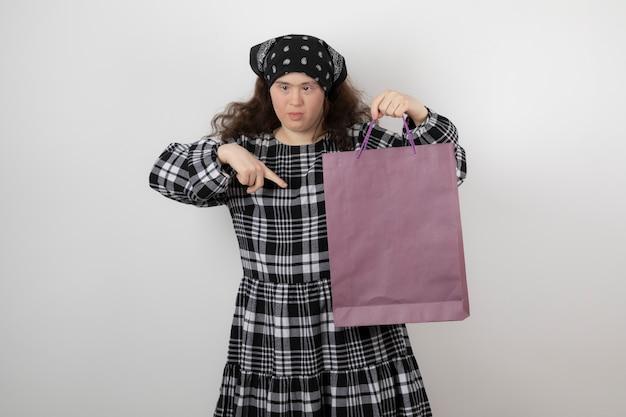 Очаровательная маленькая девочка с синдромом дауна, держащая хозяйственную сумку.