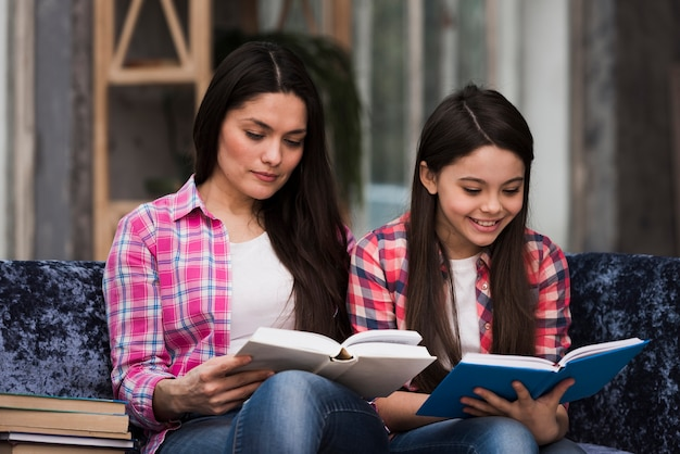 Adorable young girl and woman reading books