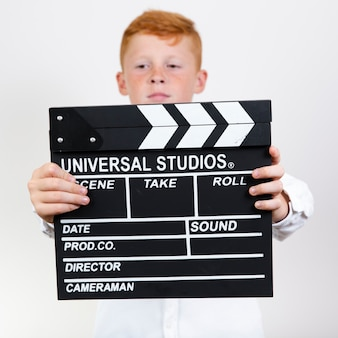 Adorable young kid holding clapperboard