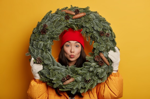 Adorable young korean woman keeps lips rounded, looks through green spruce wreath, wears yellow coat and white gloves, decorates house before christmas, poses indoor.