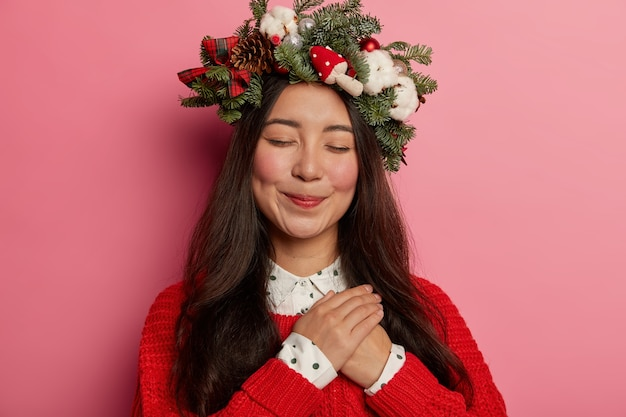 Adorabile giovane donna sorride piacevolmente indossando una festosa corona sulla testa
