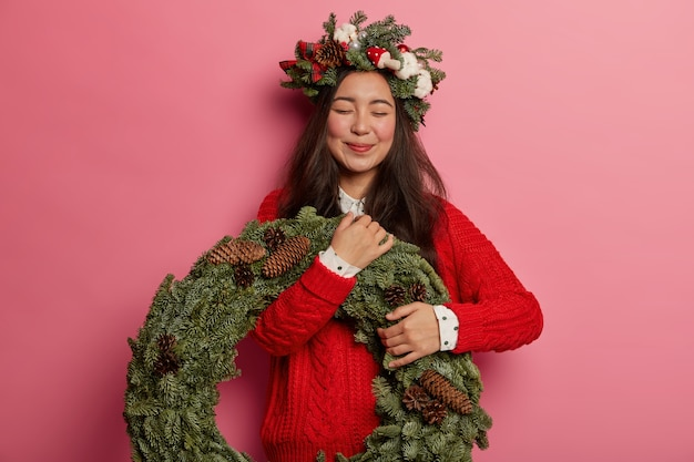 Adorable young lady smiles pleasantly wearing festive wreath on head
