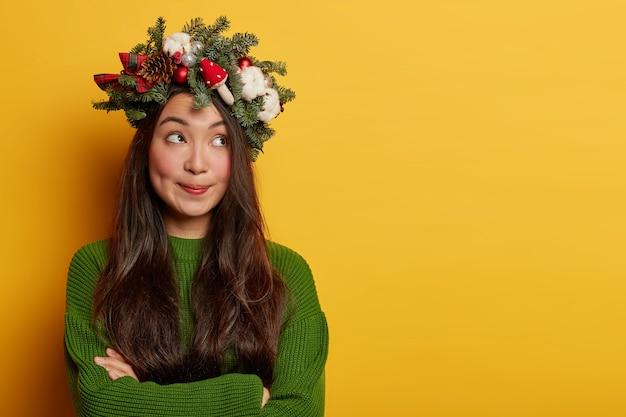 Очаровательная барышня приятно улыбается в праздничном венке на голове