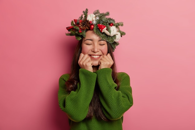 머리에 축제 화환을 즐겁게 입고 사랑스러운 젊은 아가씨 미소