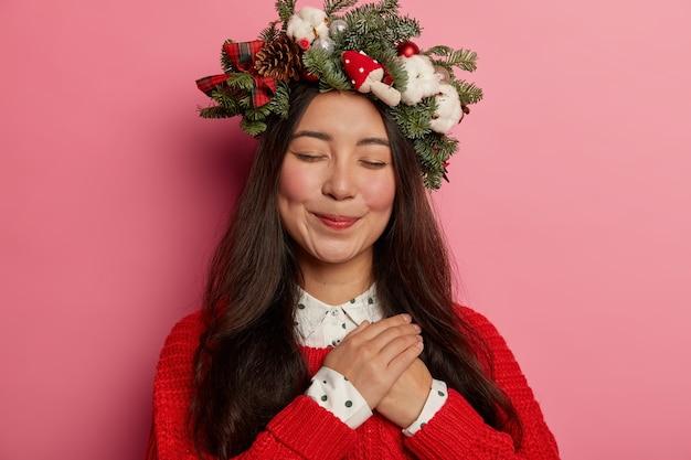 愛らしいお嬢様がお祭りの花輪を頭にかぶって気持ちよく微笑む